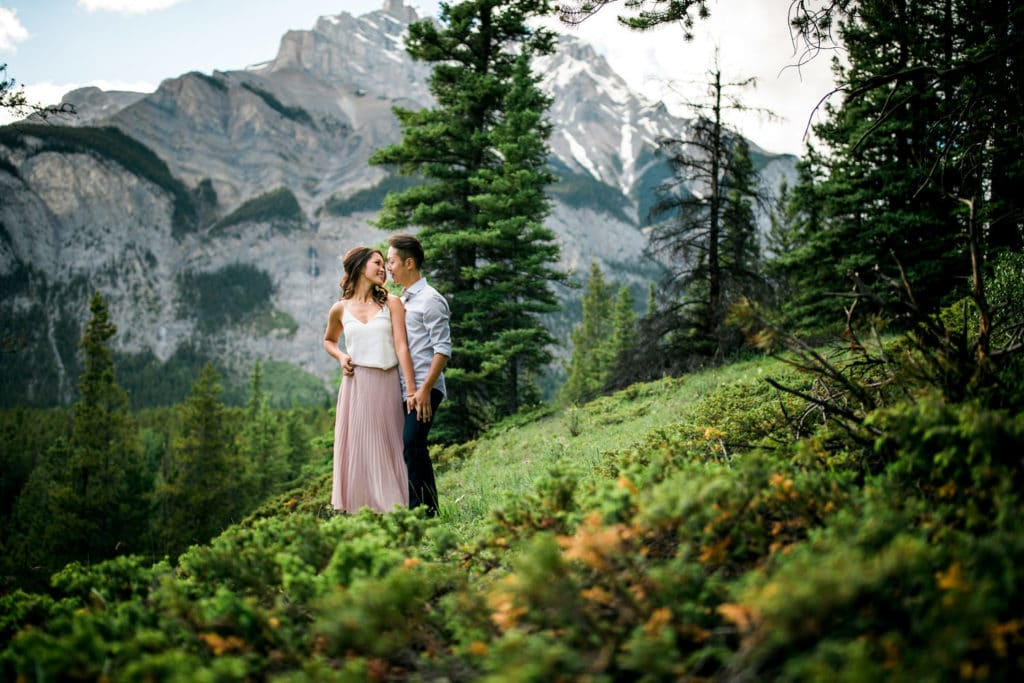 Banff Cascade Mountain engagement photographer with an engaged couple holding each other in the Canadian Rockies