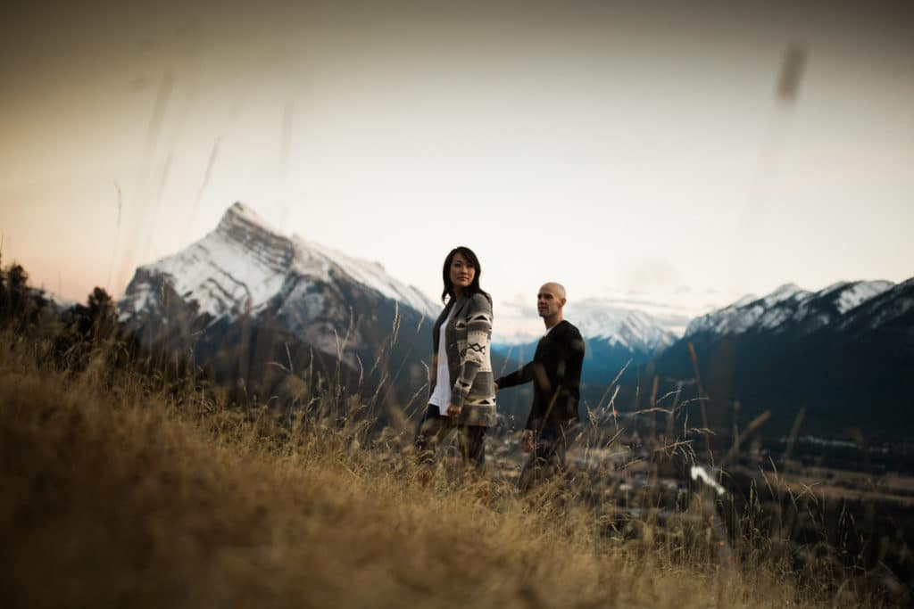 Engaged couple walking up a hill overlooking downtown Banff with Mount Rundle in the background
