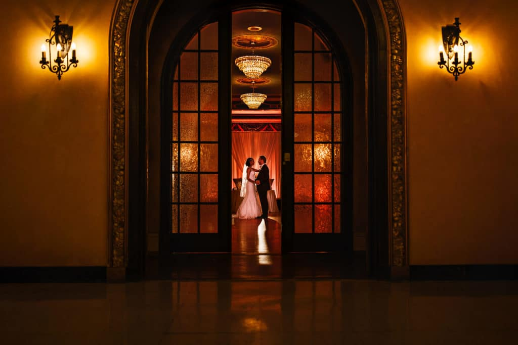 Bride and groom holding each other during their reception at the Banff Springs Hotel between doors