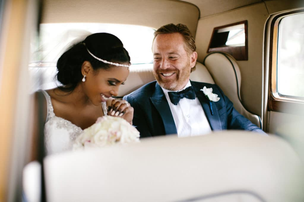 A bride and groom are inside a Bentley outside of the Banff Springs Hotel
