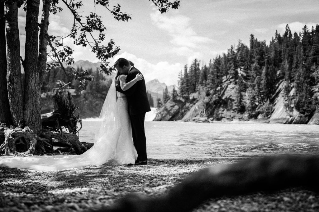 Bride and groom celebrate their wedding at Bow Falls in Banff National Park captured by Banff wedding photographer Geoff Wilkings Photographer