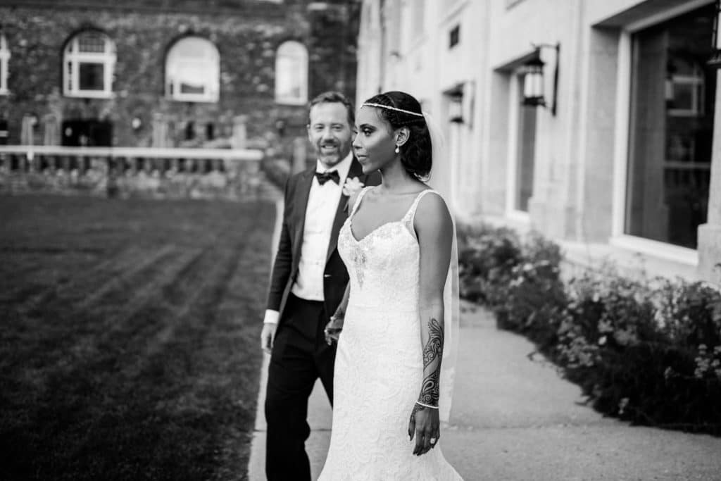 Bride walking on the grounds at the Banff Springs Hotel with her Groom as they hold hands photographed by Banff premiere wedding photographer