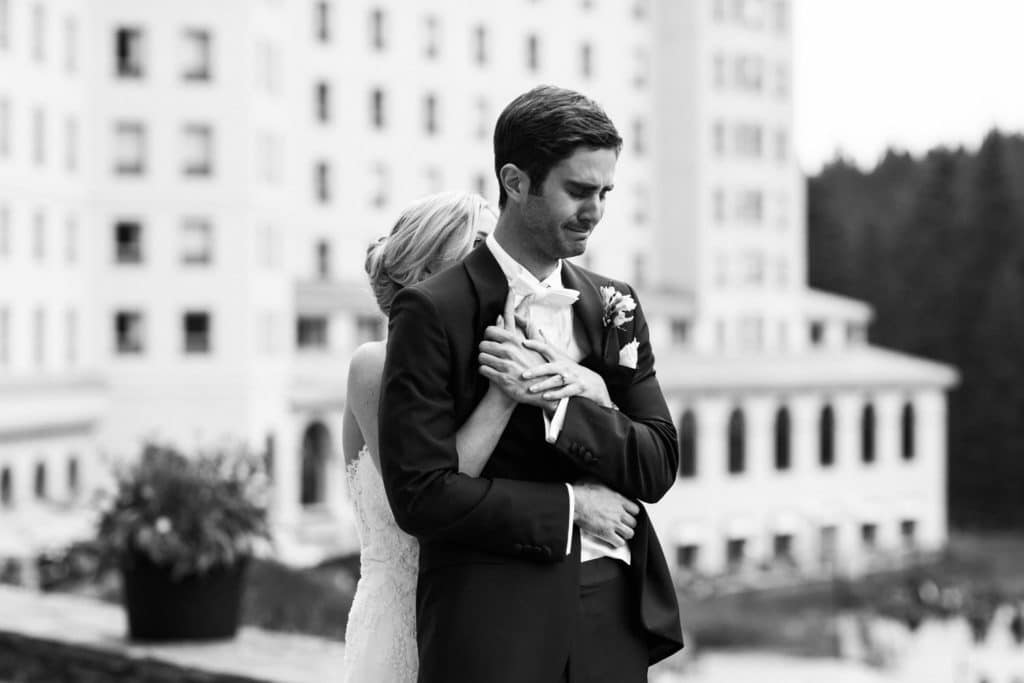 Located on the grounds of the Fairmont Chateau Lake Louise a bride is hugging the groom during their first look