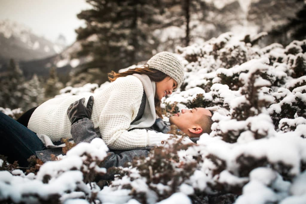 Banff engagement photographer capturing engaged couple with Cascade Mountain the background during the winter month with snow around the couple