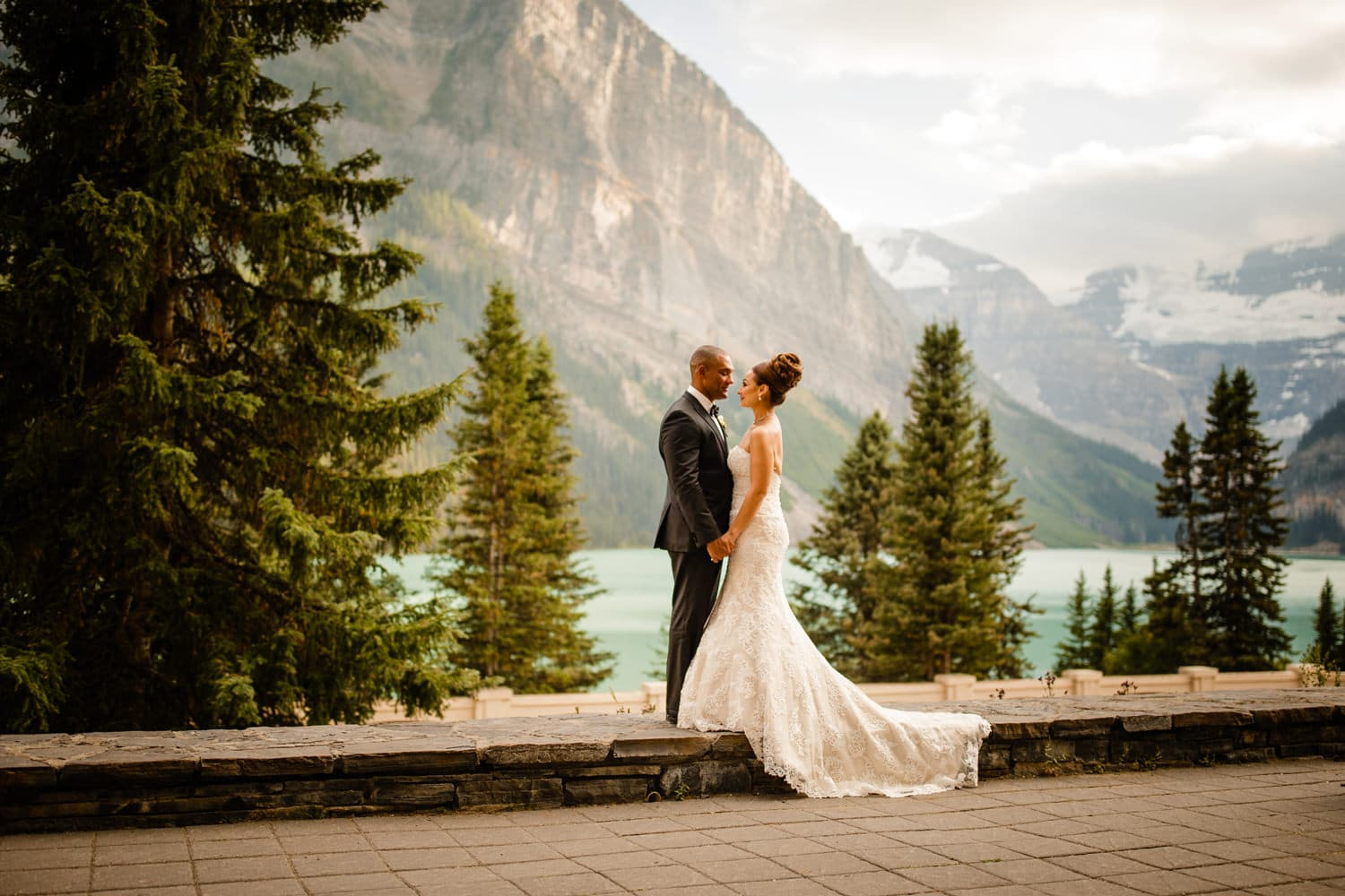 Groom and Bride on a wall located at Lake Louise with Victoria Glacier in the backgroud