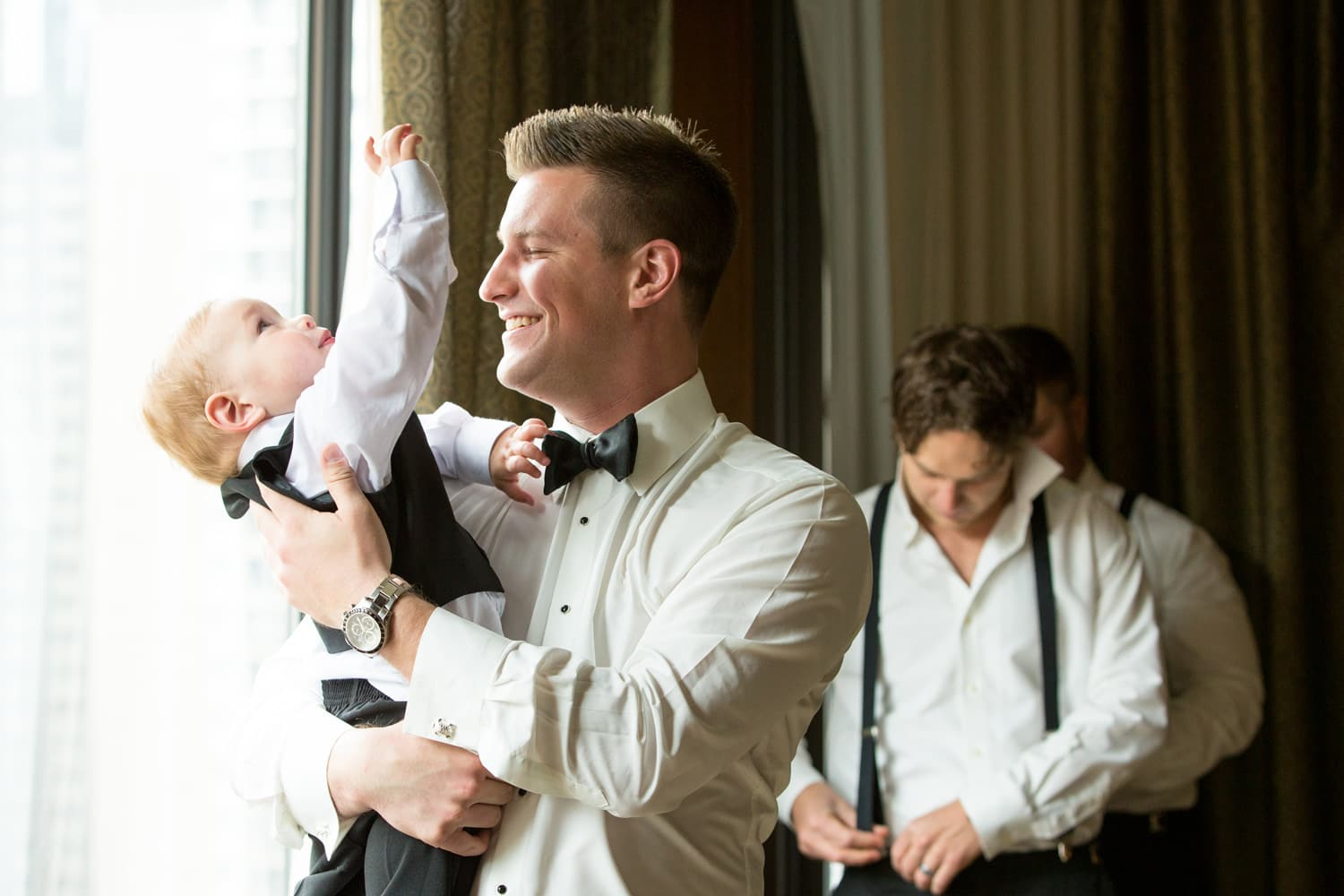 Unposed wedding photography of the groom playing with a child