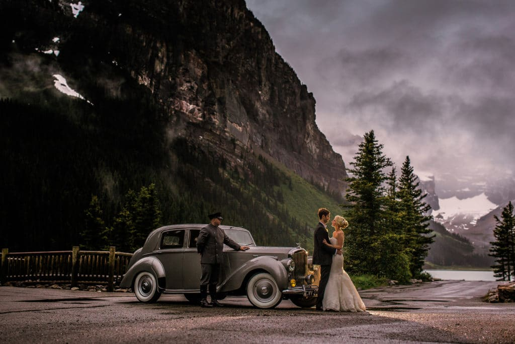 A bride and groom hold each other beside a Bentley car beside the Fairmont Chateau Lake Louise Hotel