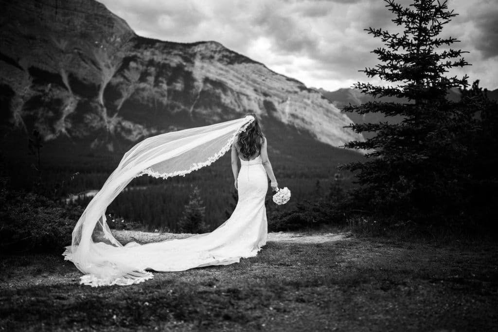 A bride is standing in Banff National Park looking at Mount Rundle after she got married at the Banff Springs Hotel