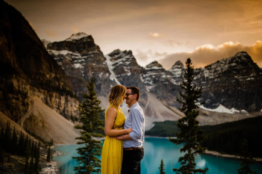 engagement photograph of a couple by Moraine Lake surrounded by The Valley Of The Ten Peaks
