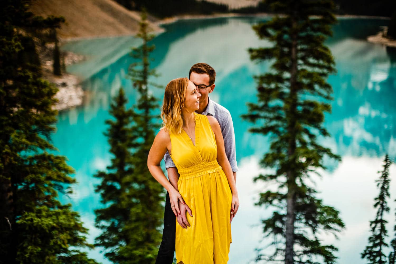 A couple shoot with the gorgeous turquoise colour of Moraine Lake behind the couple in Banff National Park