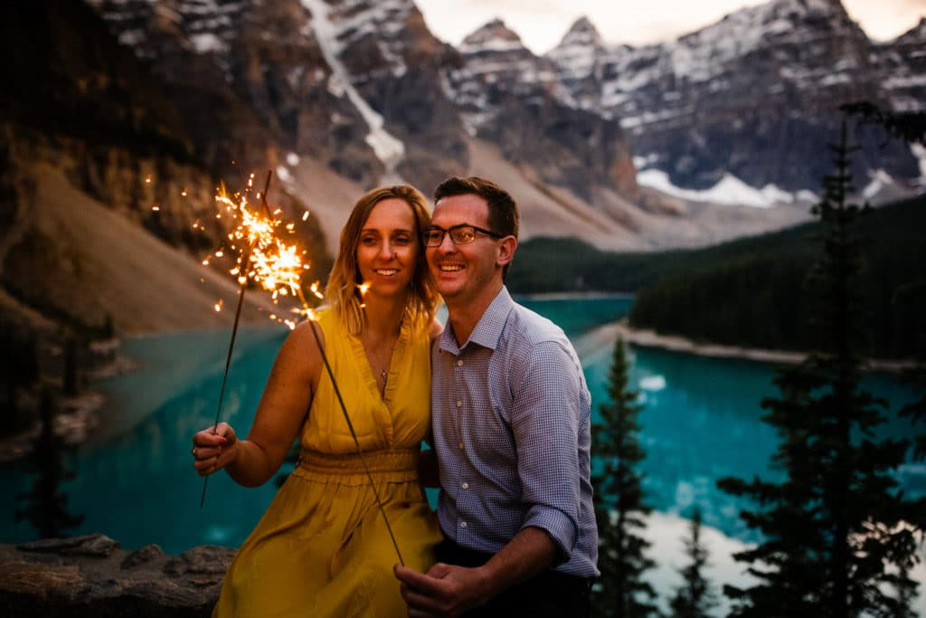A couple holding sparklers together and having fun at Moraine Lake surrounded by the Valley Of The Ten Peaks