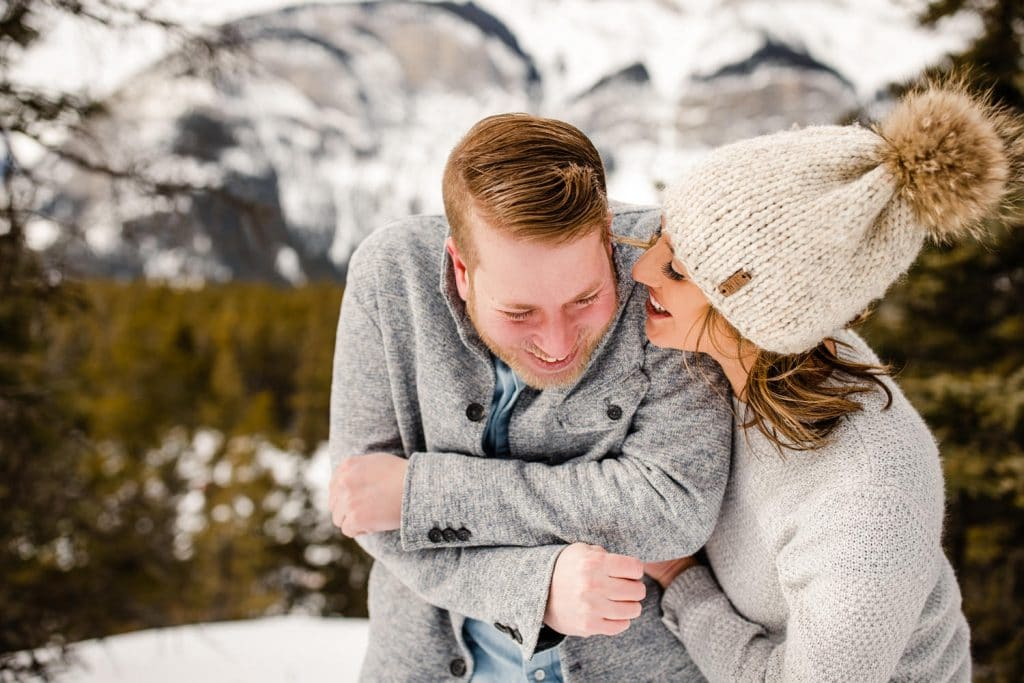 a photograph of an engaged couple laughing together in Banff National Park