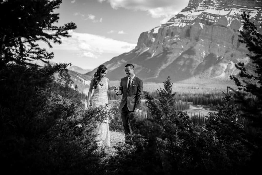 A newlywed couple walk in Banff National Park photographed by Banff wedding photographer capturing Mount Rundle in the background