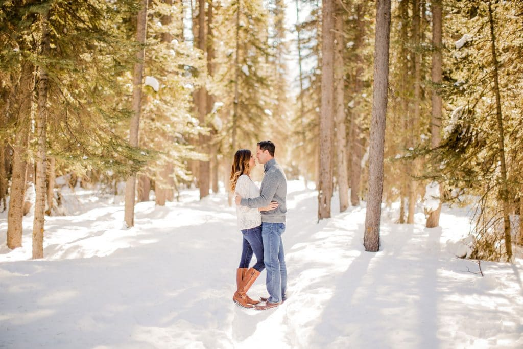 An engaged couple laugh together by trees close to Lake Louise