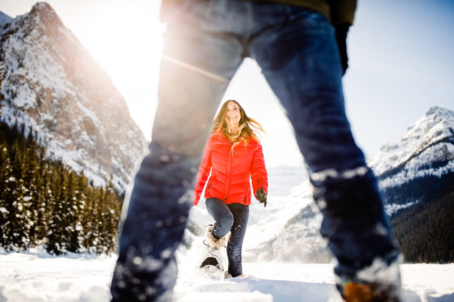 Frozen Lake Louise photo of and engagement session with the couple playing in the snow.