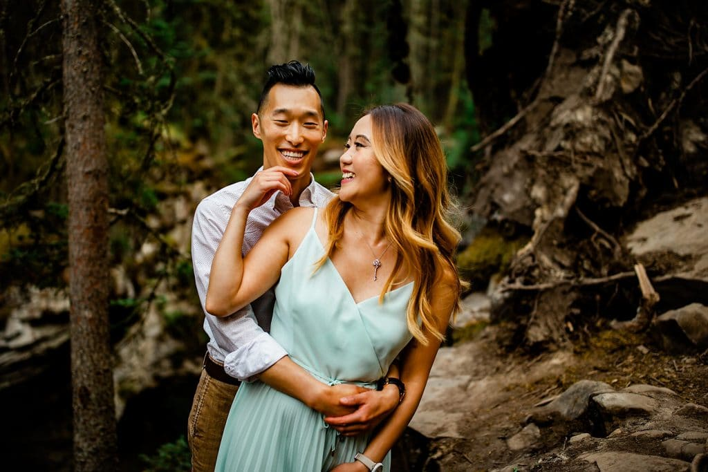 Photograph of an engaged couple at Johnston Canyon laughing and playing together