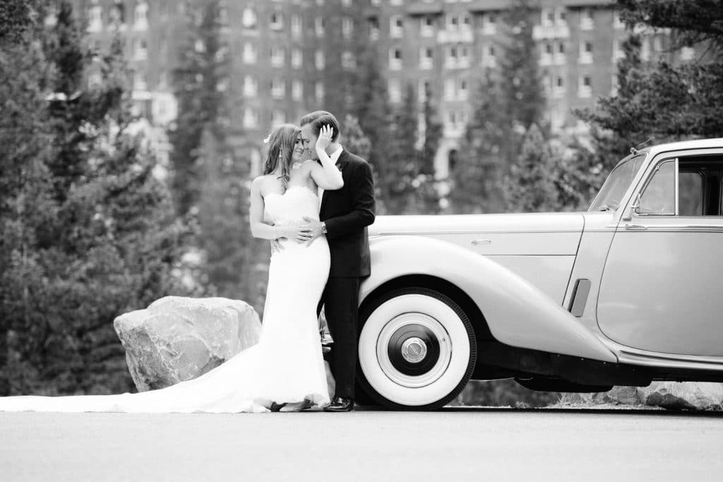 Vintage Bentley car with a bride and groom leaning on it with the Banff Springs in the background