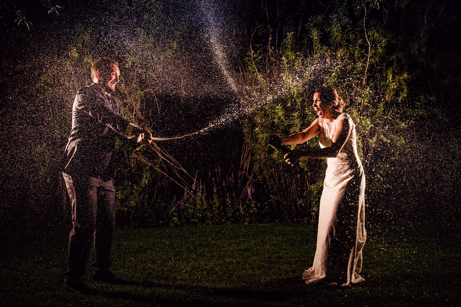 A bride and groom spraying champagne