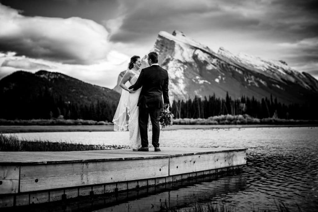 Banff Vermilion Lake wedding photograph with bride and groom on the dock with Mount Rundle in the background