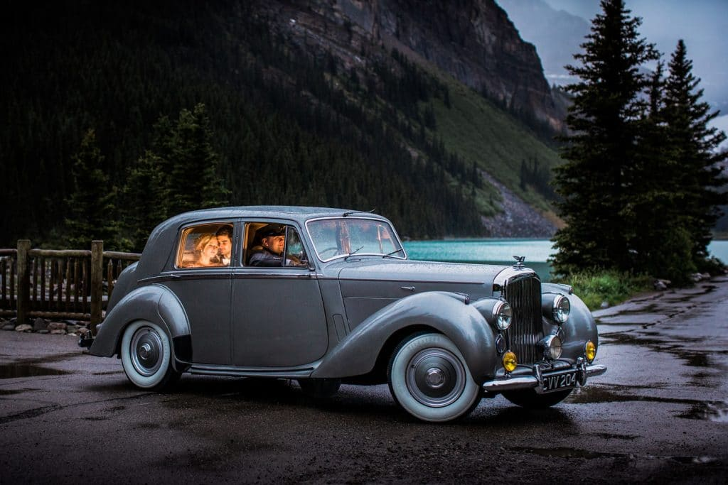 Groom and bride site inside their private Bentley outside the Chateau Lake Louise Hotel