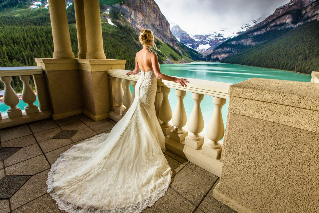 Bride Getting Ready at the Belvedere Suite Chateau Lake Louise hotel as she looks over Lake Louise with Victoria Glacier in the distance
