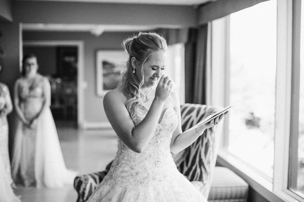 Calgary wedding photographer captures a moment of the bride crying as she reads a love note from the groom on her wedding day in Calgary