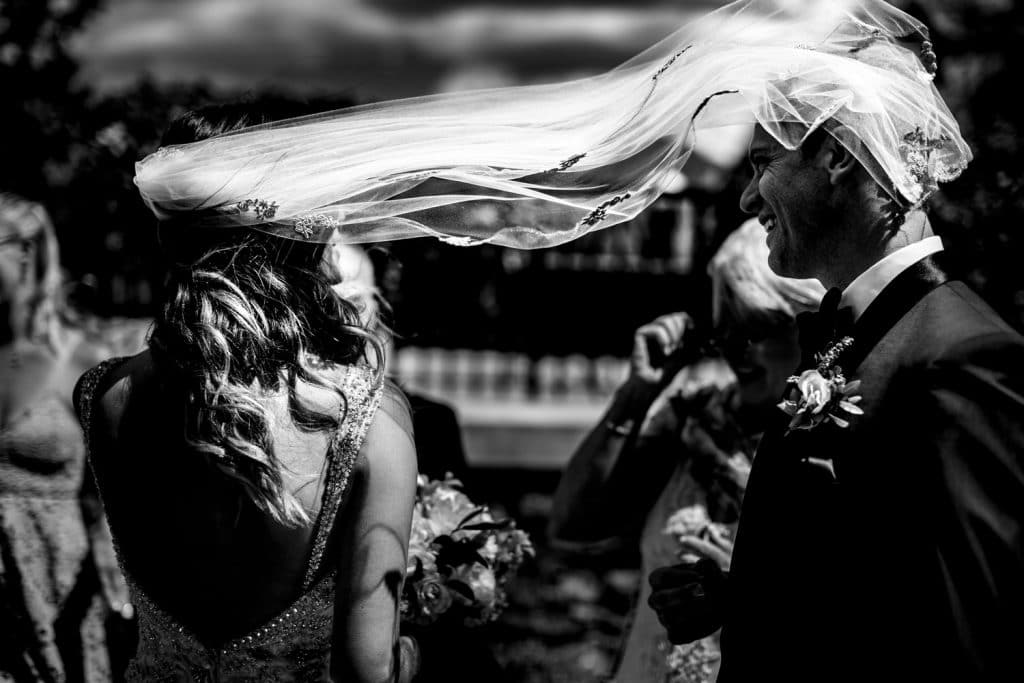 bride and groom laughing together as the wind picks up and catches the brides veil after their wedding ceremony Banff Springs wedding