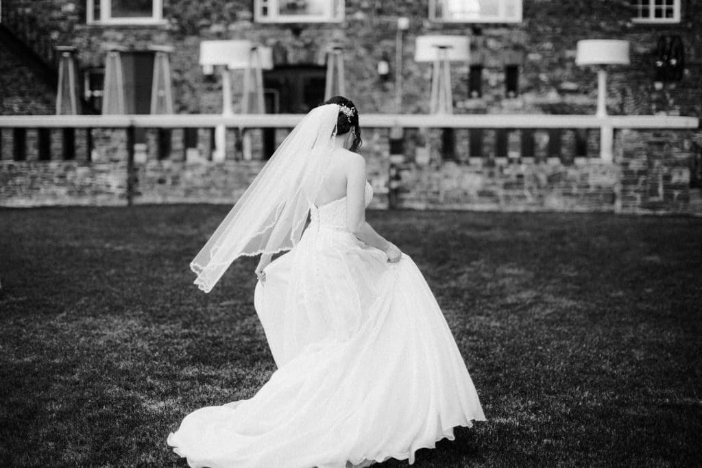 Bride walks by herself on the ground of the Banff Springs Hotel with her dress flowing