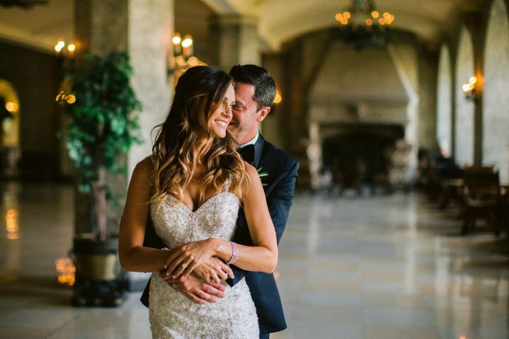 Banff wedding photographer photographs a groom and bride inside the Banff Springs Hotel holding each other