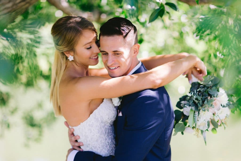 brides arms are over her groom shoulders in Calgary during a portrait photography shoot at the Calgary Golf Country Club