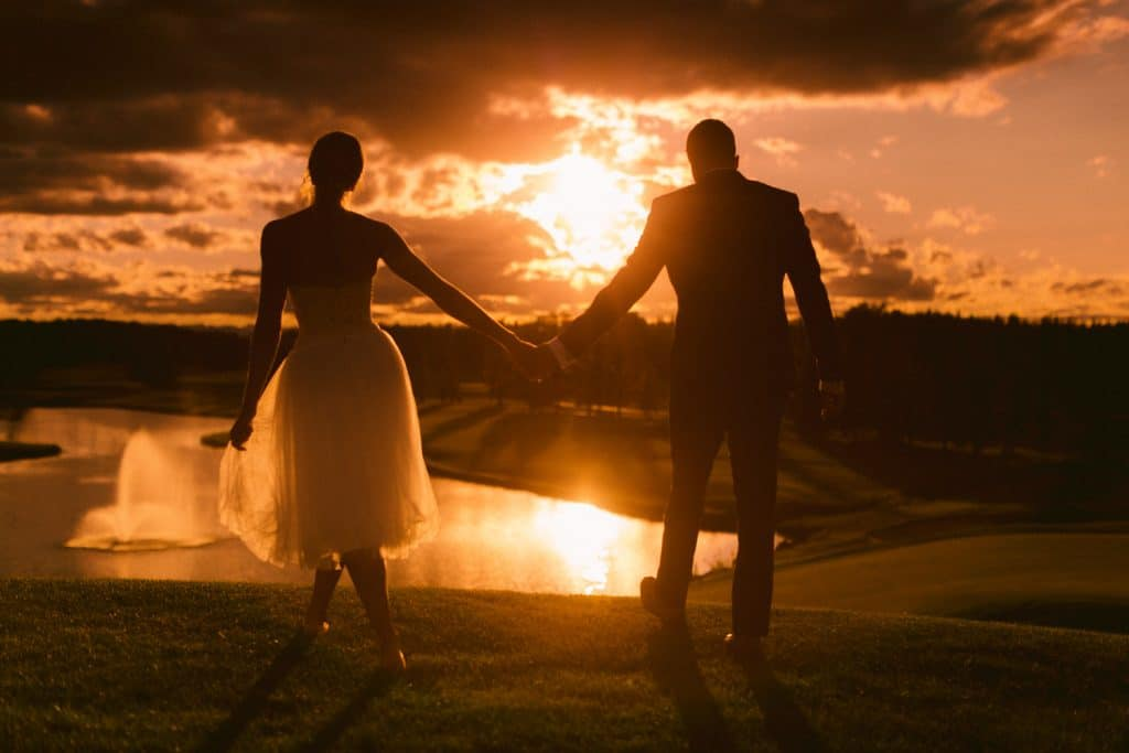 Calgary golf course photograph of a bride and groom holding hands at sunset after the wedding reception photographed by Calgary wedding photographer Geoff Wilkings Photographer