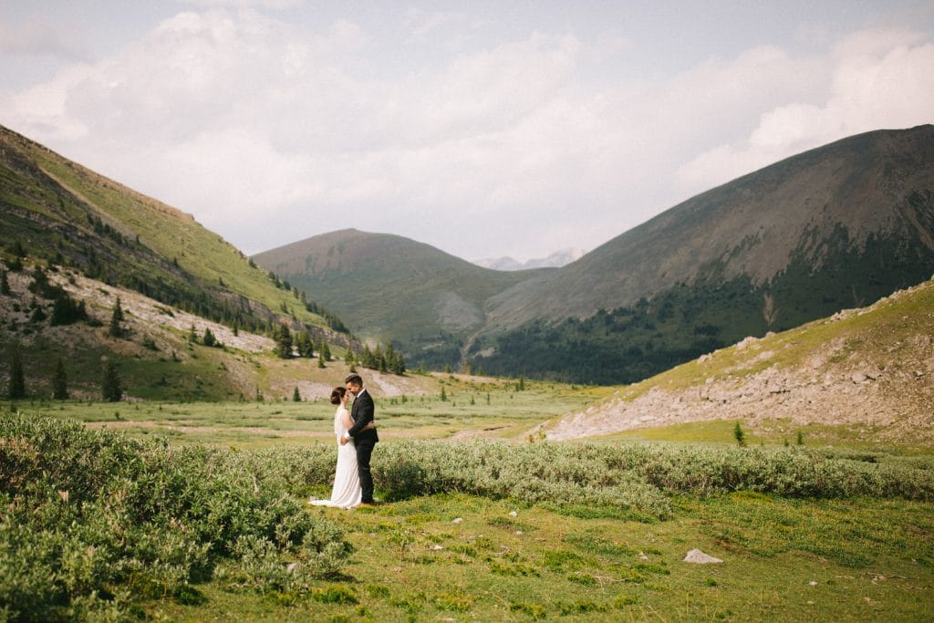 Within the mountain meadows in Canmore Alberta a photograph captures a moment between the bride and groom surrounded by the alpine Canadian Rockies