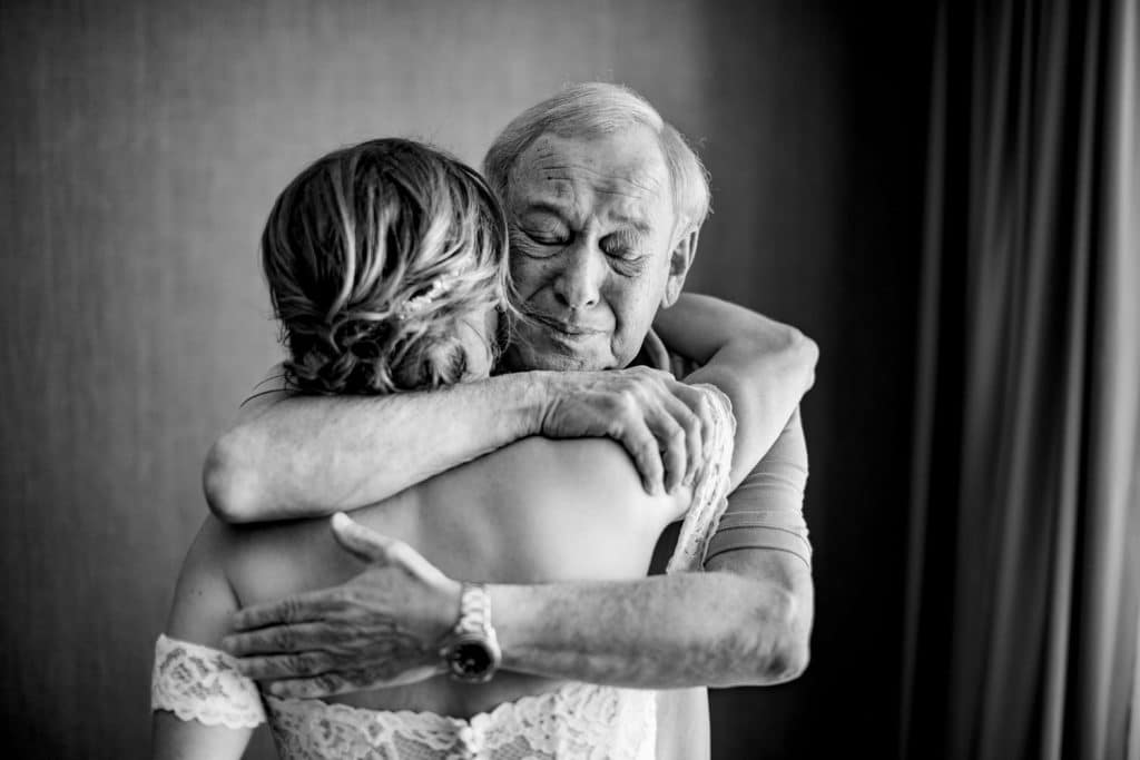 Father hugging the bride during their first look