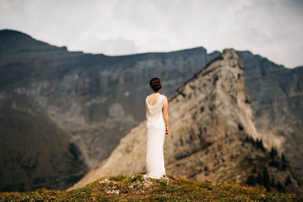 bridal portrait of a bride standing mountain top in Canmore during her elopement