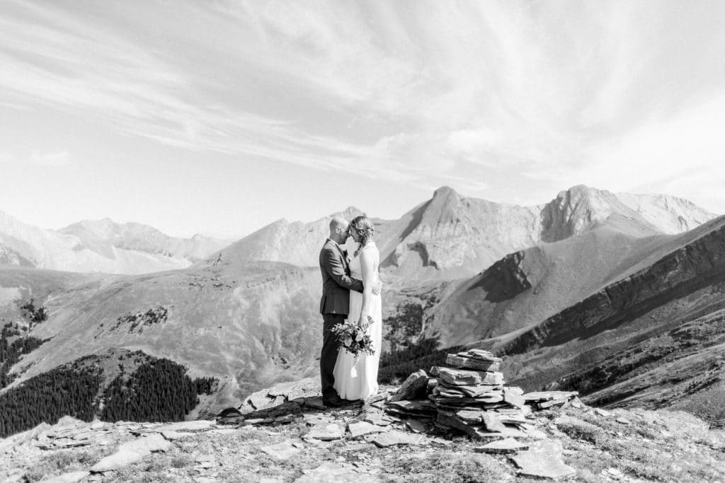 A bride and groom holding each other at the top of a Canmore mountain after they said their vows to each other during their helicopter wedding
