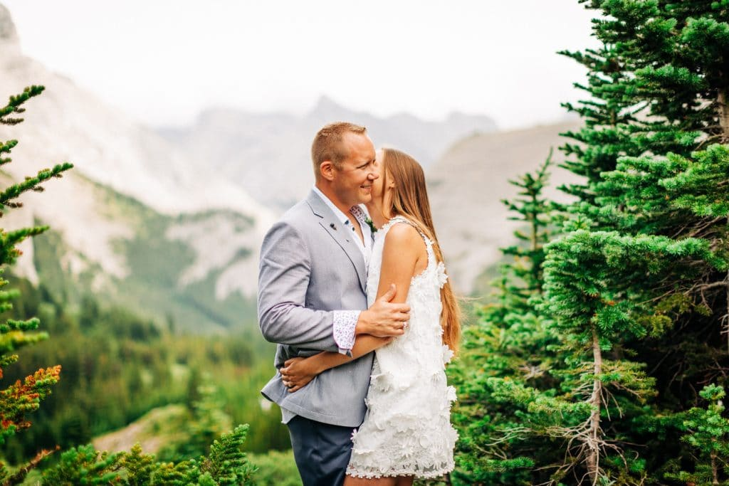 groom tickles his bride during a helicopter mountain elopement photography portrait