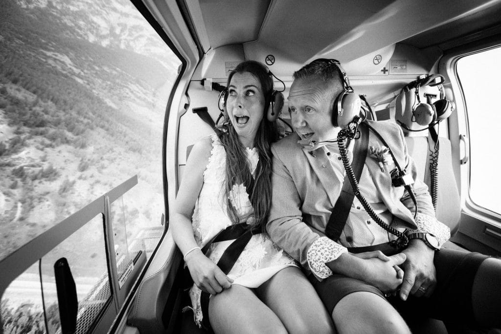 Bride and groom laughing inside a helicopter after getting married in Canmore
