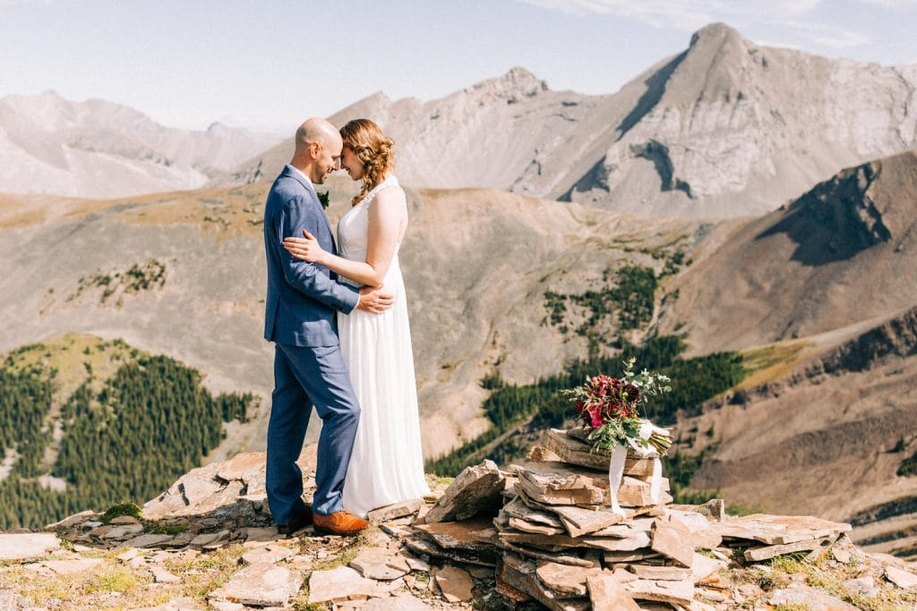 an elopement mountain top photograph in Canmore at the top of a mountain between a bride and groom after their elopement ceremony