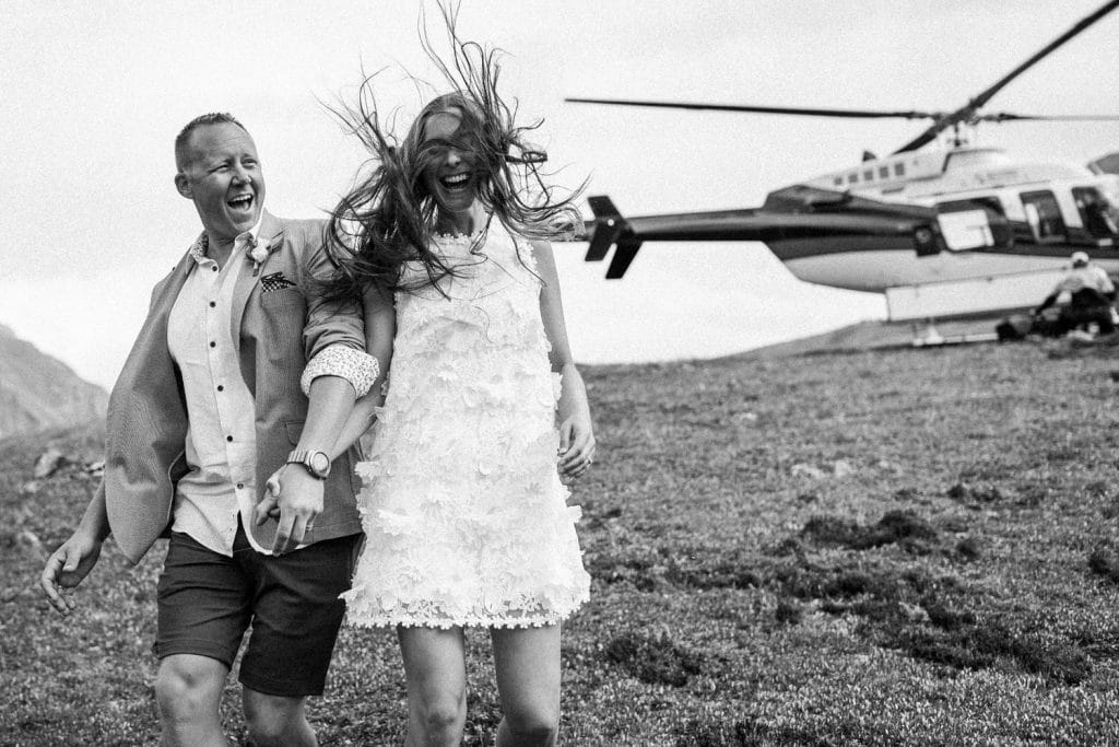 Bride laughs as the Alpine helicopter in Canmore lands with the brides hair flying in the air