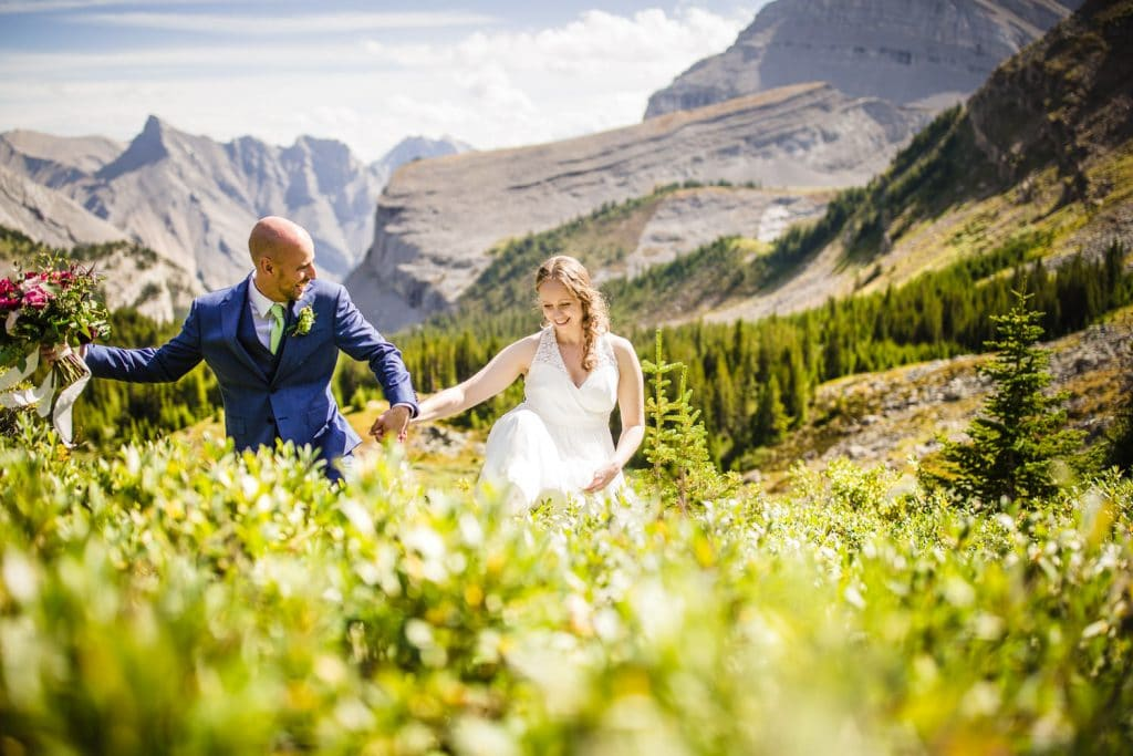 Canmore wedding photographer captures a moment between a bride and groom walking in the long grass during their helicopter Canmore mountain elopement