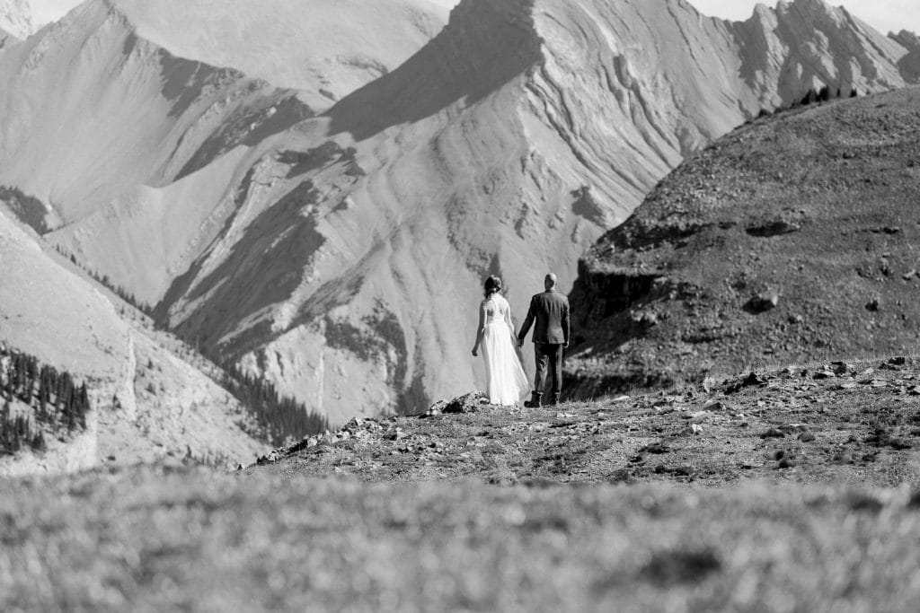 Bride and groom walk away into the distance as we wait for our private helicopter to fly back to Alpine Canmore Alberta