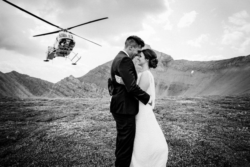 A helicopter is landing in the background during a helicopter mountain Canmore wedding