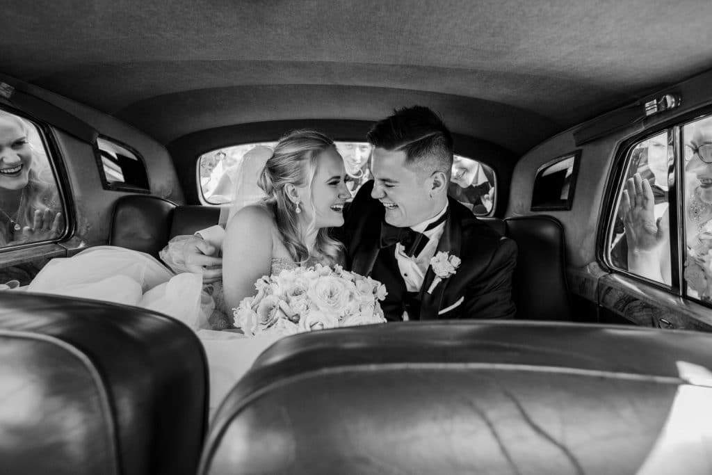 Bride and Groom laughing in a car with the bridal party outside