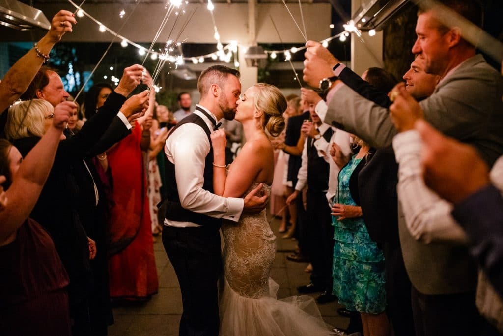 Photograph at Alloy Restaurant in Calgary during a wedding reception with guests holding sparklers as they kiss