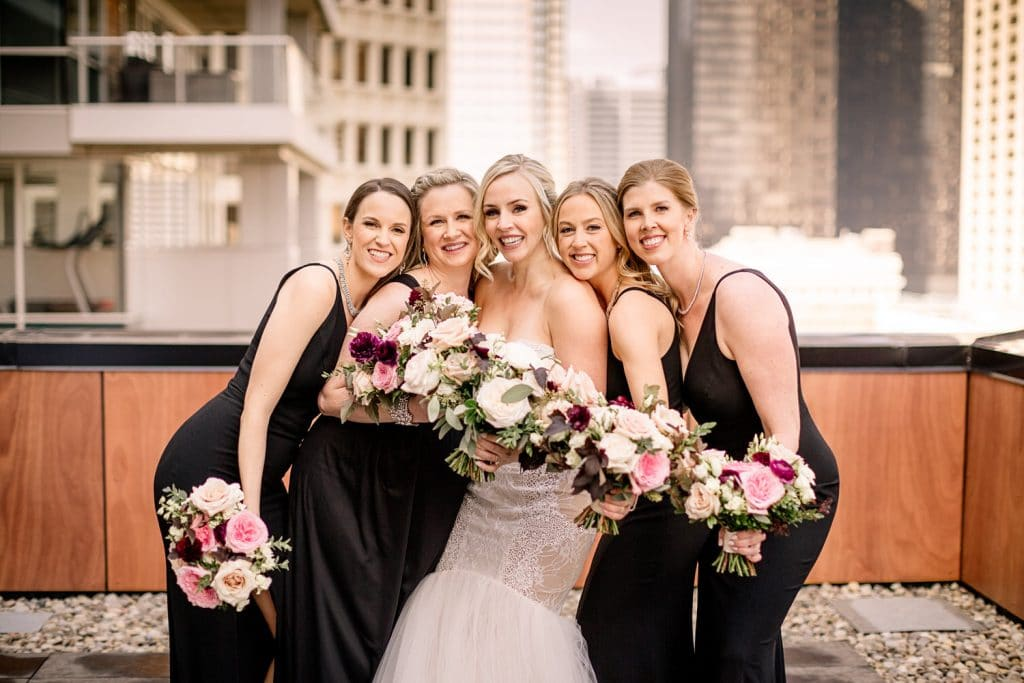 Bridal party and bride laughing at a top Calgary hotel as they are photographed by Calgary's best Calgary wedding photographer