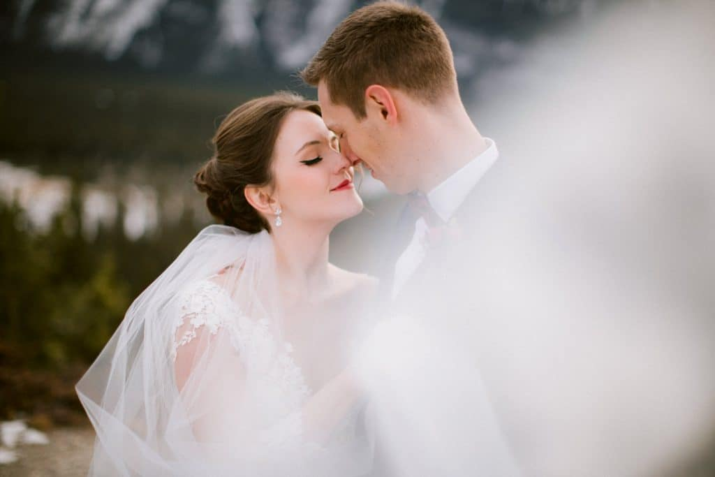 a wedding veil is flowing in Banff National Park as the bride and groom touch each other photographed by Banff wedding photographer