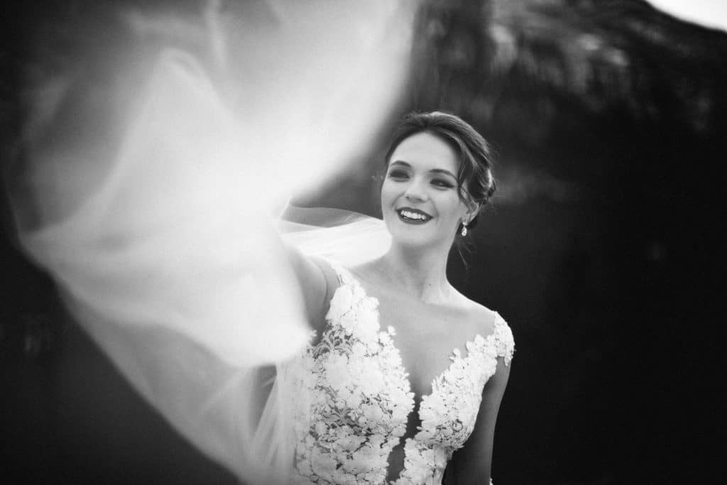 a black and white photograph of a bride playing with her wedding veil in Banff National Park