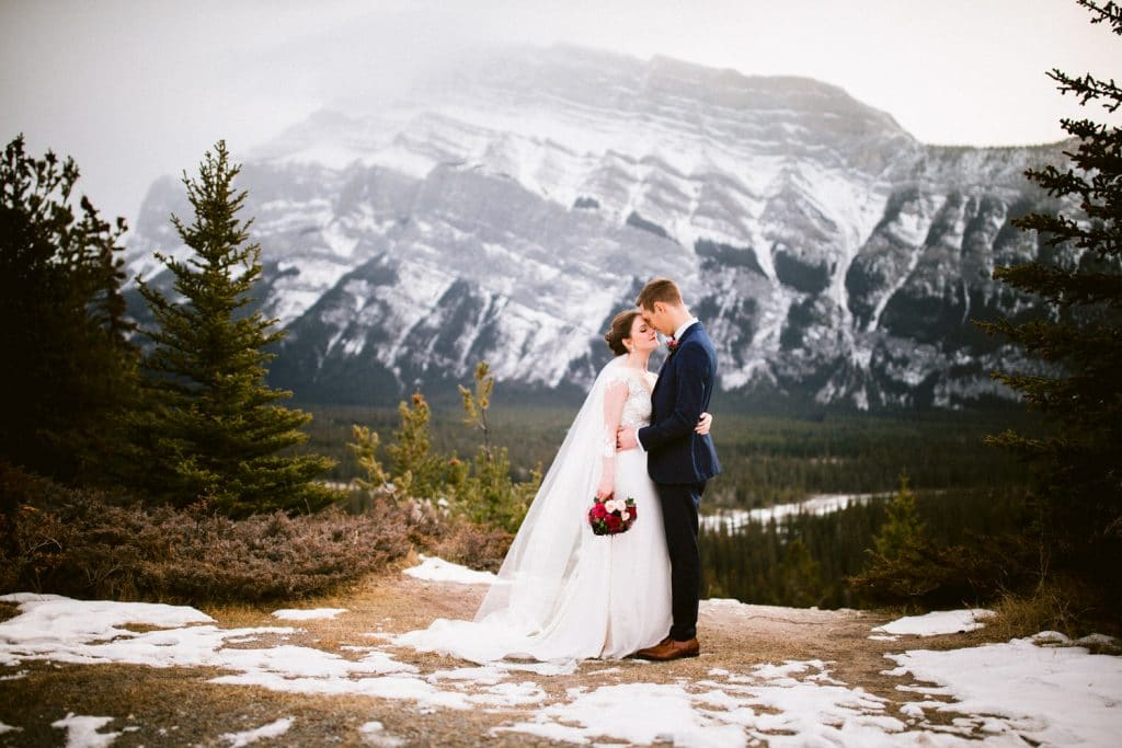 Bride and groom holding each other in Banff National Park with Mount Rundle in the background