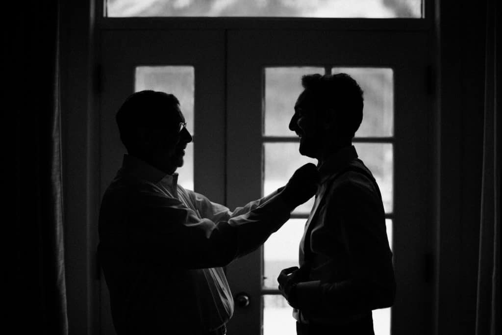 Father of the groom helps his son the groom get ready at Chateau Lake Louise Hotel