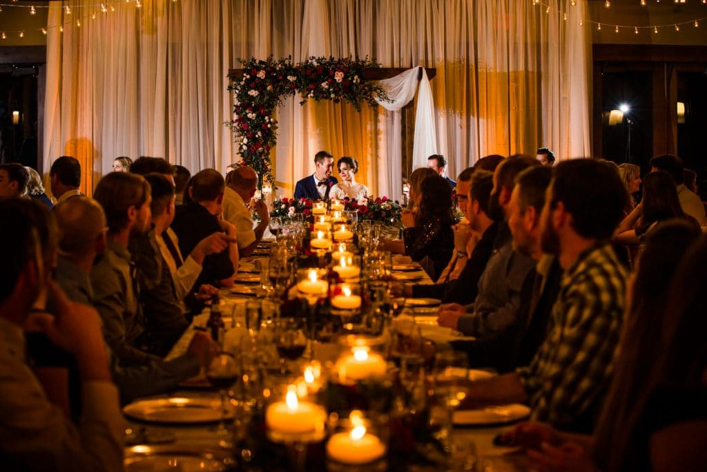 Silvertip Resort wedding reception photograph with the bride and groom holding each other during speeches photographed by Canmore wedding photographer